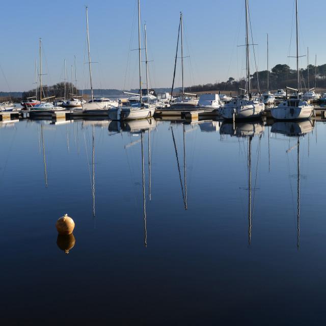 """Sailboats Moored on lake at sunrise"" stock image"