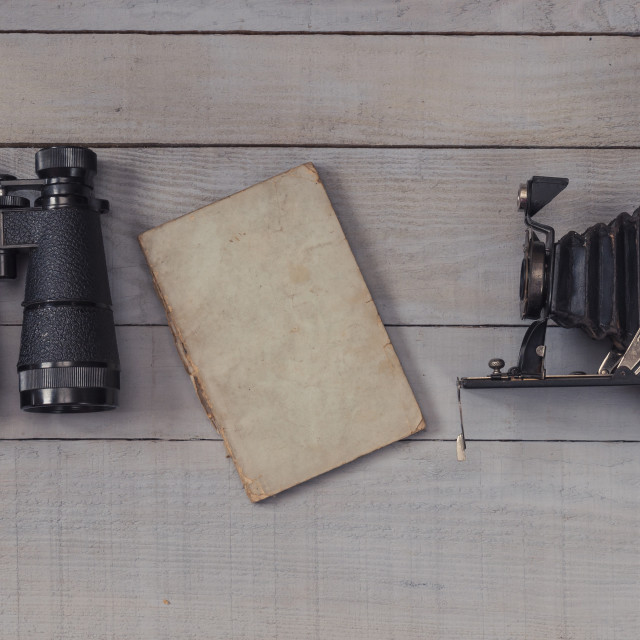 """Antique binoculars, photography camera and notebook on wooden background"" stock image"