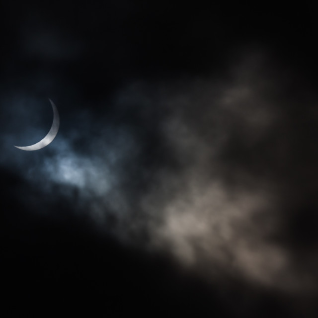 """Crescent Sun Through Clouds"" stock image"