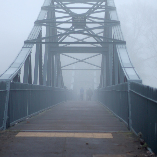 """Metal bridge and people in thick fog"" stock image"