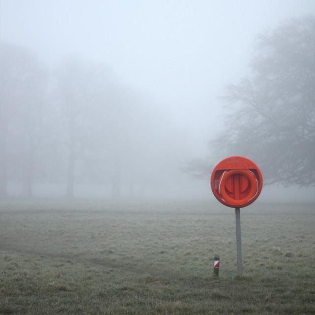 """""""Orange lifebuoy on dry land in fog"""" stock image"""