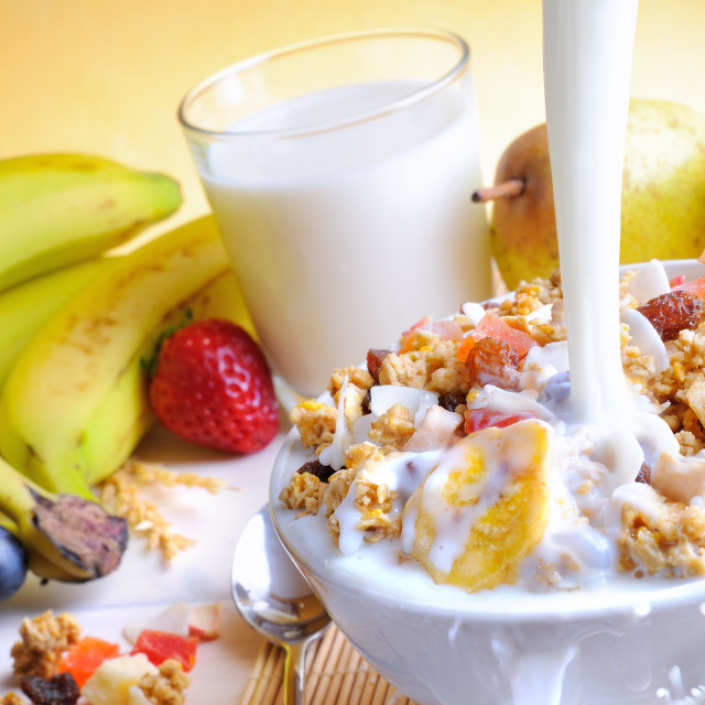 """""""Stream of milk falling into a bowl of cereal and fruits"""" stock image"""