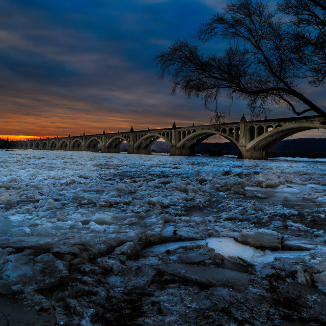 """Icy River with Bridge at Sunset"" stock image"