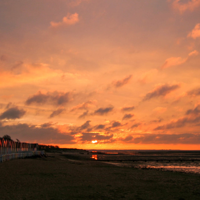 """Sun rising behind Mersea Beach Huts"" stock image"