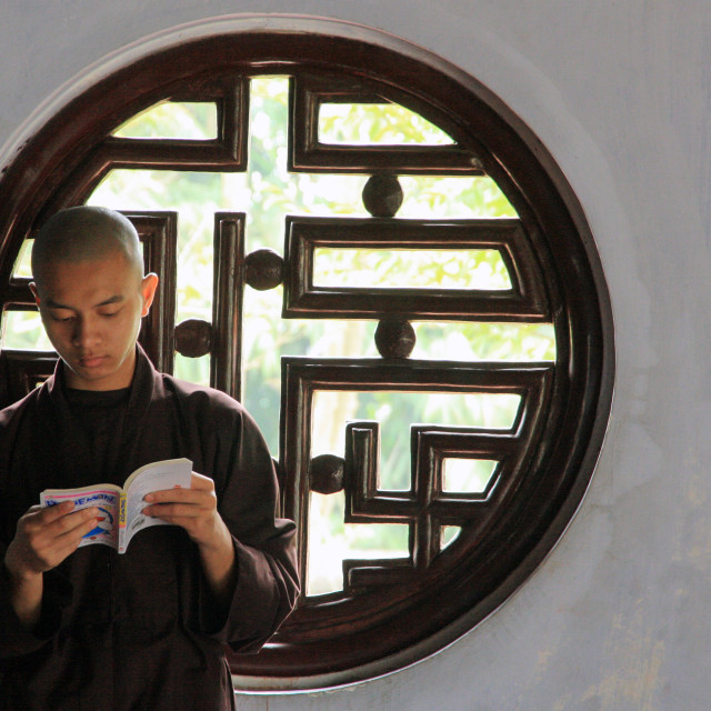 """Young Vietnamese monk studying by the round window"" stock image"