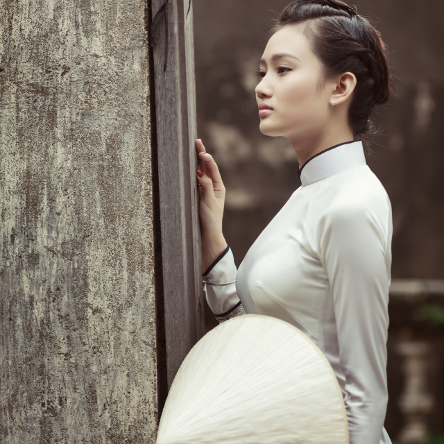 """Vietnamese young women with Ao Dai in old town"" stock image"