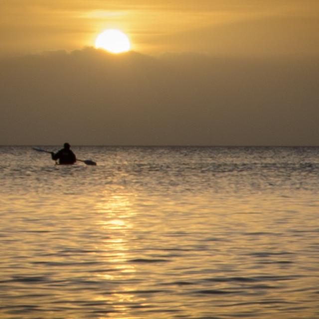 """Lone Kayaker Watching The Sunrise"" stock image"