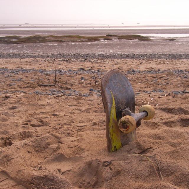 """skate board buried on beach"" stock image"
