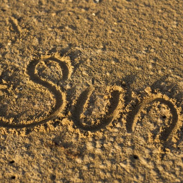 """'Sun' Written in Golden Sand"" stock image"