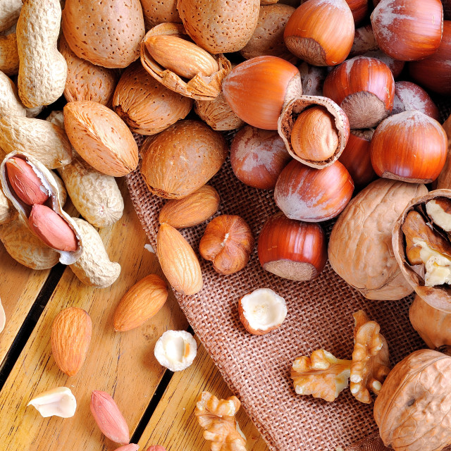 """""""Tasty nuts on a wooden table in field top view"""" stock image"""