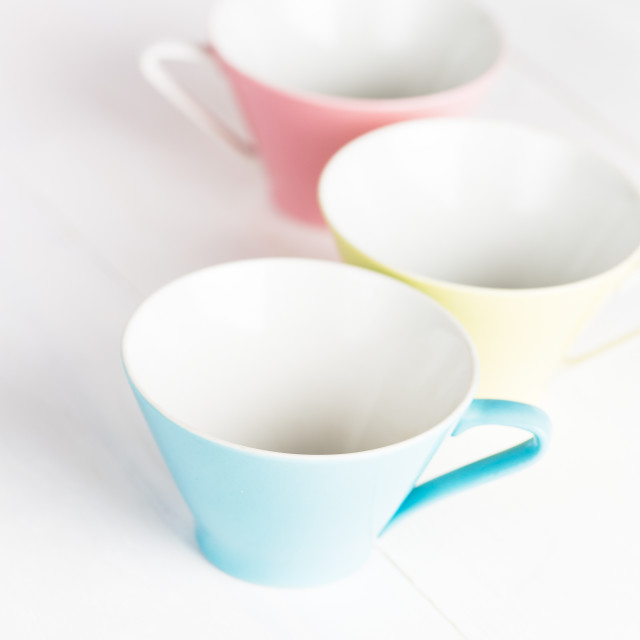 """""""Three pastel colored china coffee cups on white wood"""" stock image"""