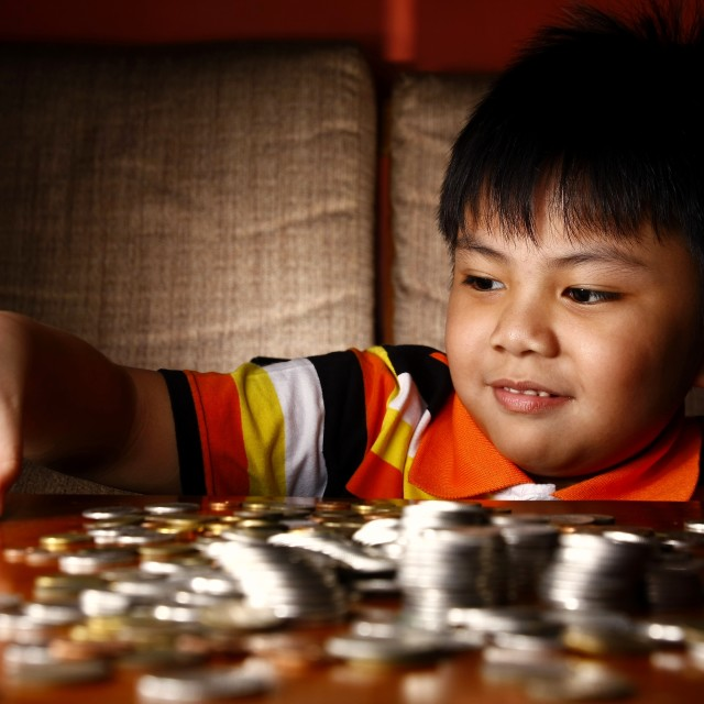 """Young Boy Stacking or Piling Coins"" stock image"