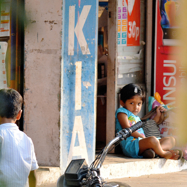 """Bored kid outside cellphone shop in India."" stock image"