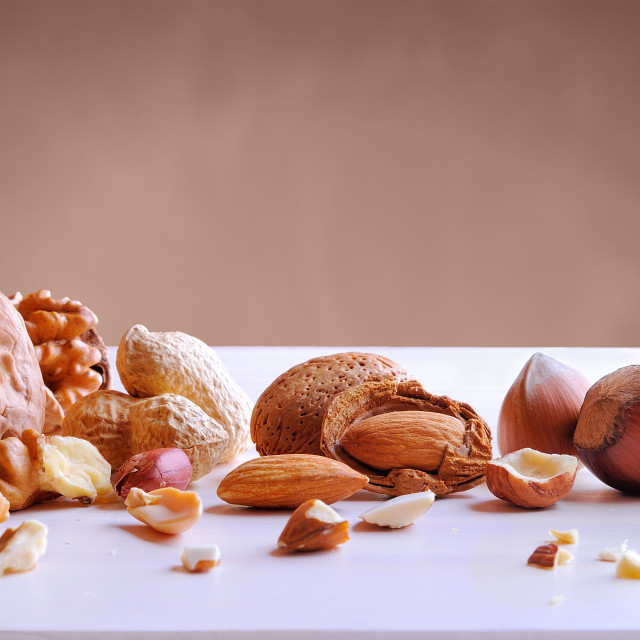 """""""Tasty nuts in shell and shelled on a white table"""" stock image"""