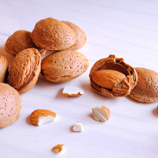 """""""Almonds in shell and shelled on a white wooden table"""" stock image"""