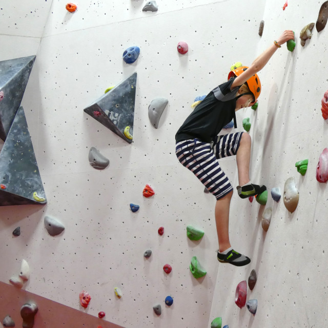 """Young girl climbing wall"" stock image"