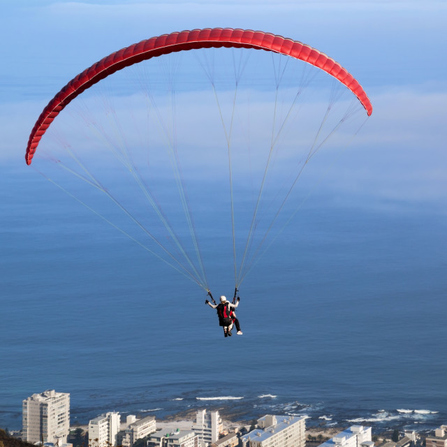 """Paraglider in Red against world of Blue"" stock image"