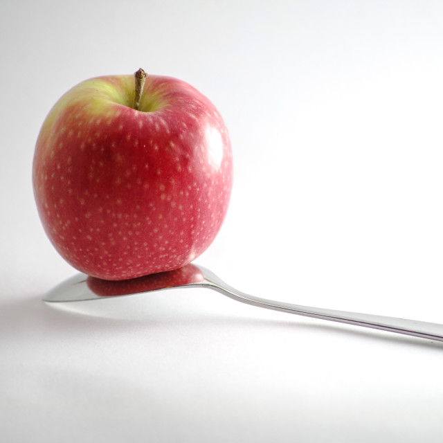 """Upside down spoon and apple"" stock image"
