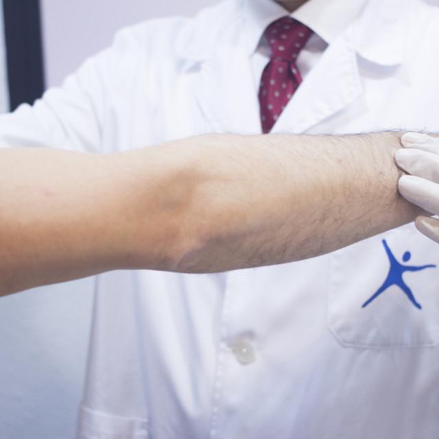 """Dooctor surgeon examines patient shoulder arm injury"" stock image"