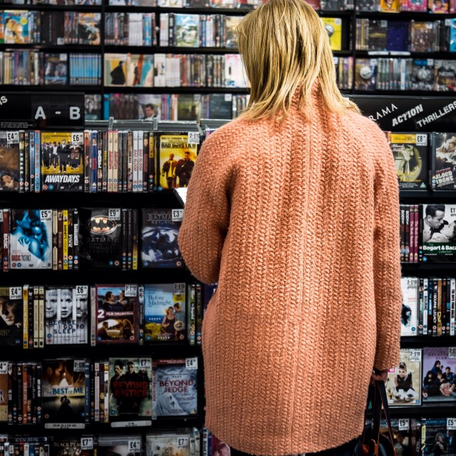 """Girl shopping for DVDs in a big store."" stock image"