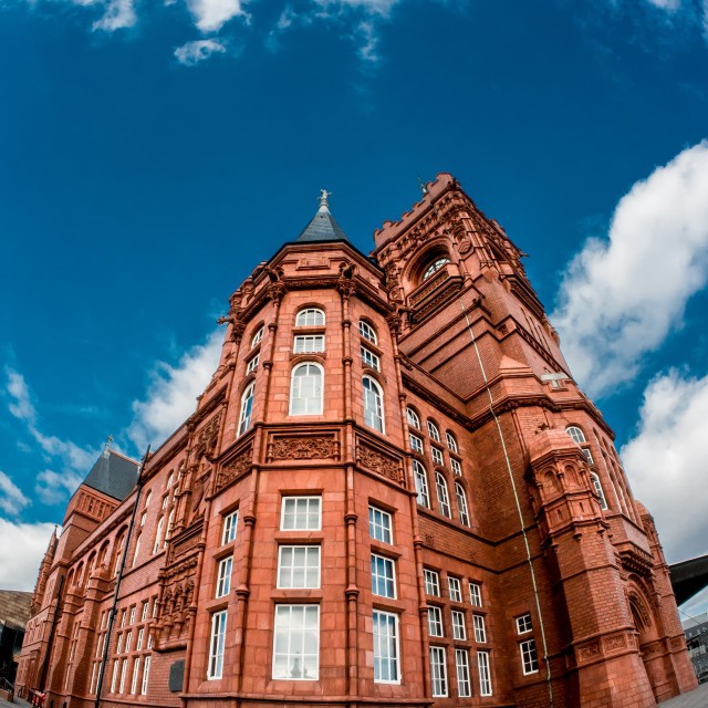 """Red brick building beneath a blue sky."" stock image"