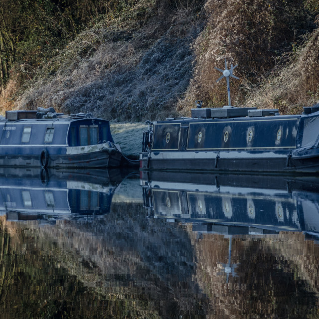 """Two frozen narrowboats and reflections"" stock image"