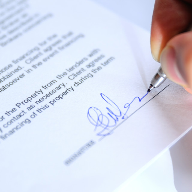 """Businessman signing a document closeup"" stock image"