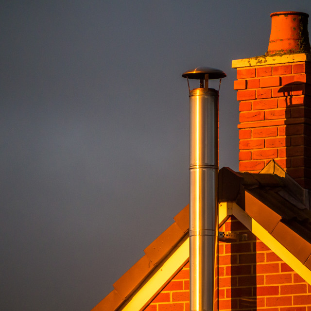 """A chimney and a wood-burning stove flue in the evening sunlight."" stock image"