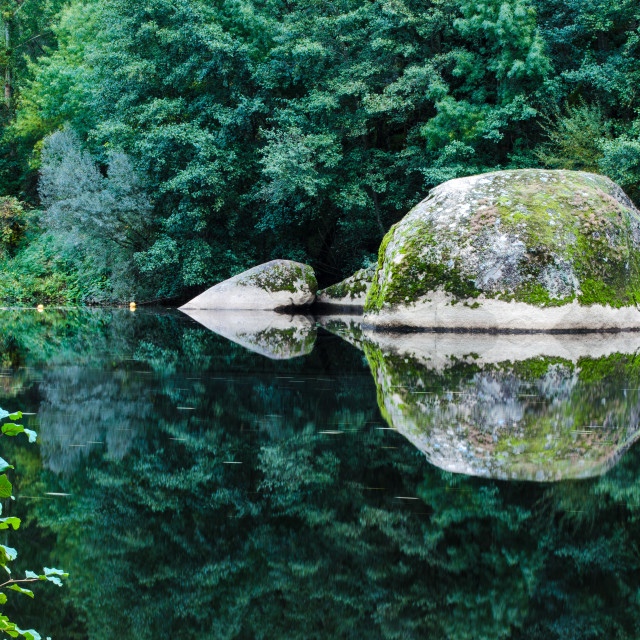 """Large granite rocks reflected in the river."" stock image"