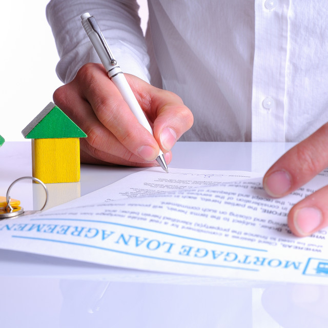 """Client signing the mortgage loan agreement with small wooden hou"" stock image"
