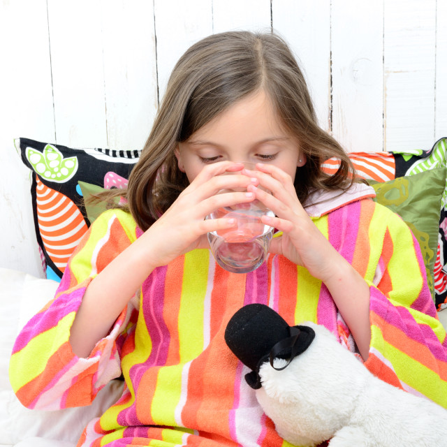 """a sick girl drinking a glass of water"" stock image"
