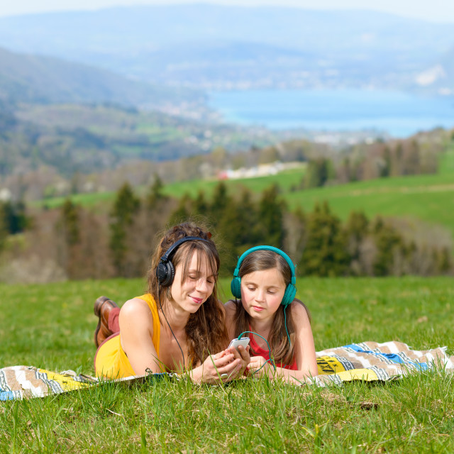 """Mom and daughter listening music in nature"" stock image"