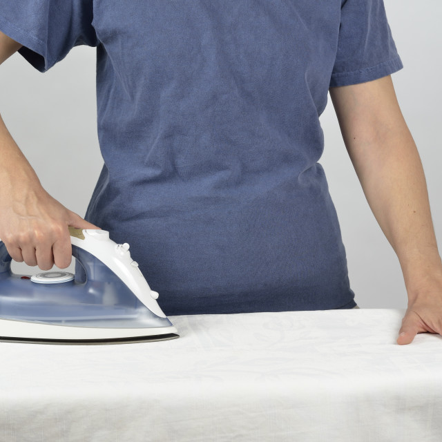 """Ironing a white tablecloth"" stock image"