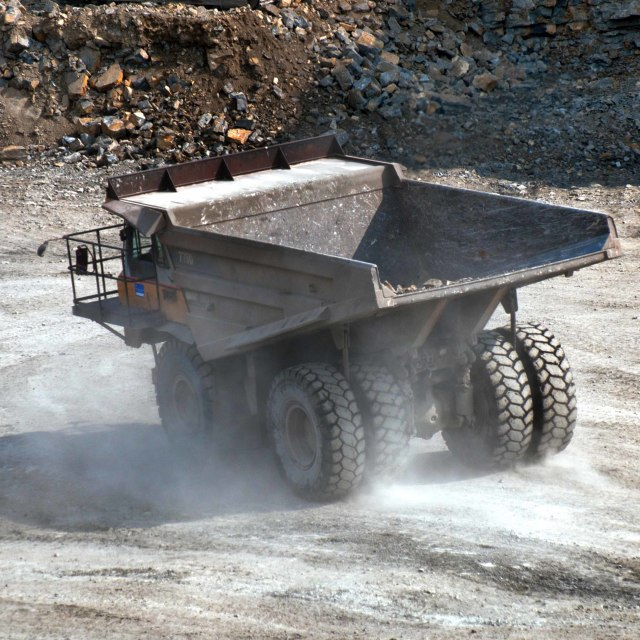 """Dump truck travelling on a road at a quarry site creating dust"" stock image"