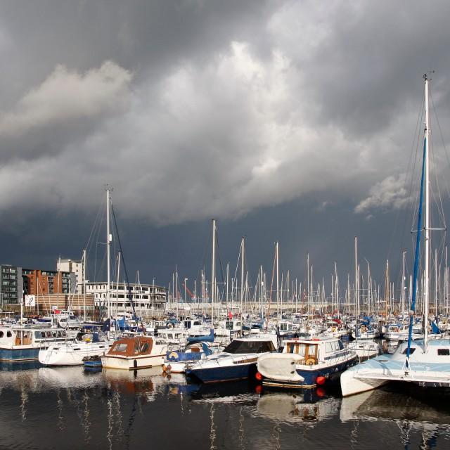 """Boats in a marina, stormy sky"" stock image"