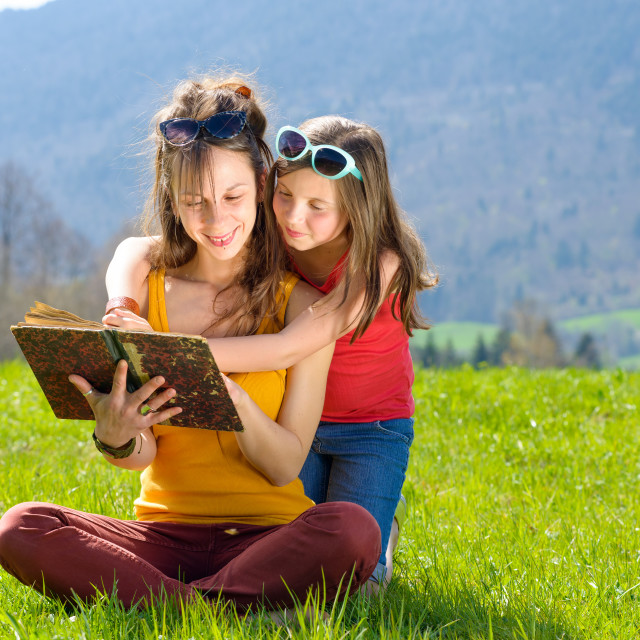 """Mom and daughter reading a book"" stock image"