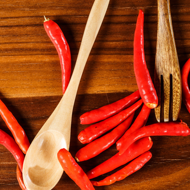 """Chilli with wooden spoon on a wooden table"" stock image"