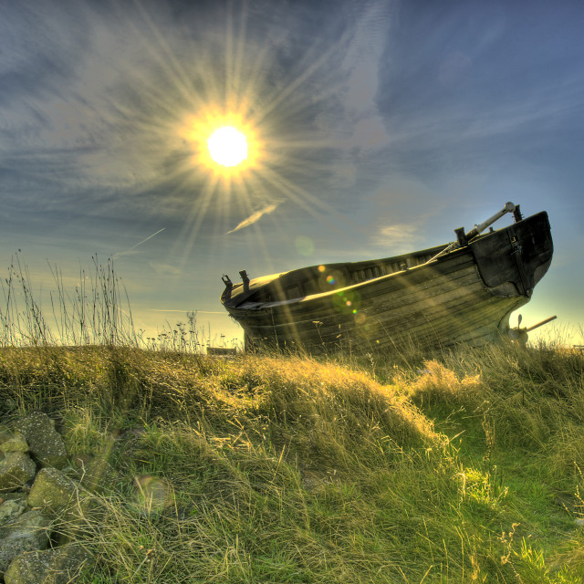 """Abandoned boat into the sun"" stock image"