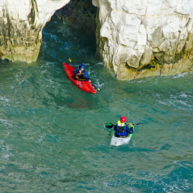 """Sea Kayaks exiting an arch"" stock image"
