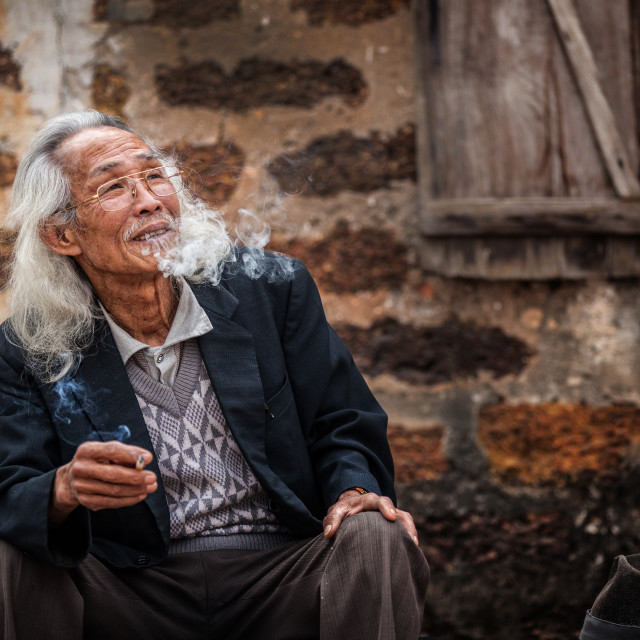 """A men smoking at Duong Lam Hanoi"" stock image"