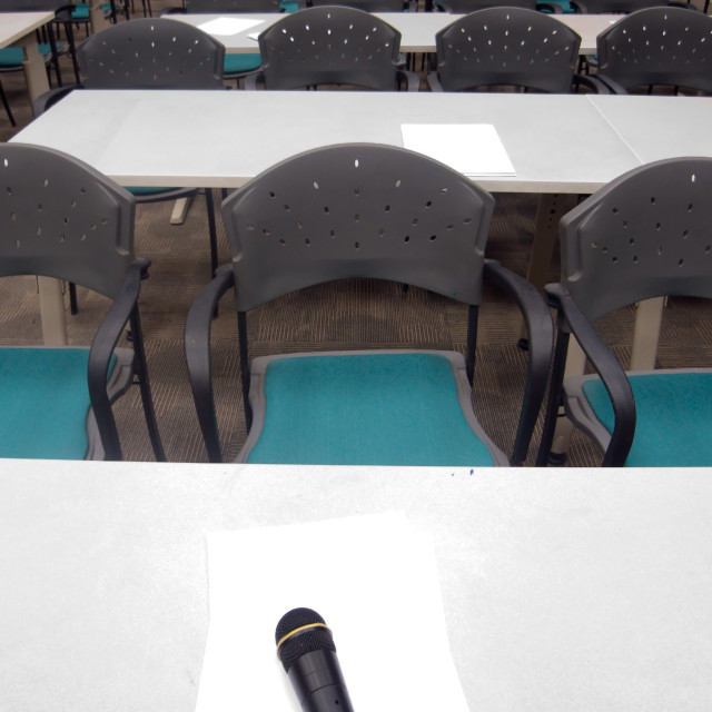 """""""Microphone, papers, table and chairs in a room"""" stock image"""