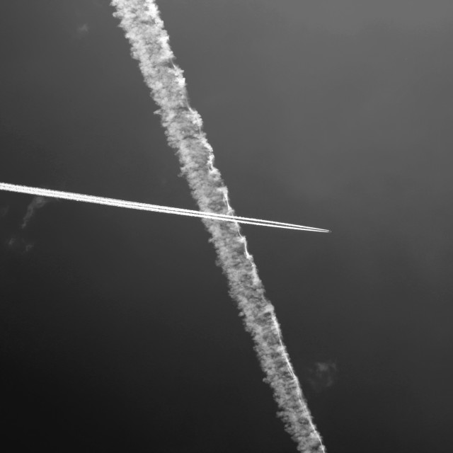 """""""Passenger jet trails crossing in a blue sky"""" stock image"""