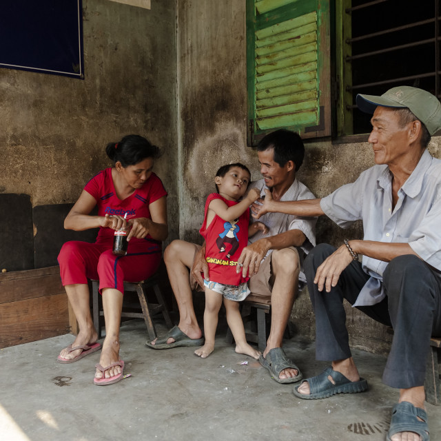 """A Vietnamese Family at their front yard in the ancient quarter"" stock image"
