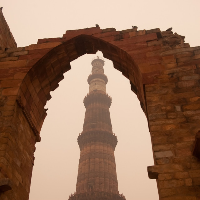 """The Qutub Minar framed by remains of a stone wall"" stock image"