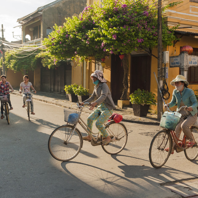 """Women driving bicycles through a crossroad in Hoi An"" stock image"