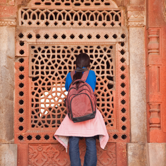 """Girl peering into the latticed wall at Humayun Tomb"" stock image"