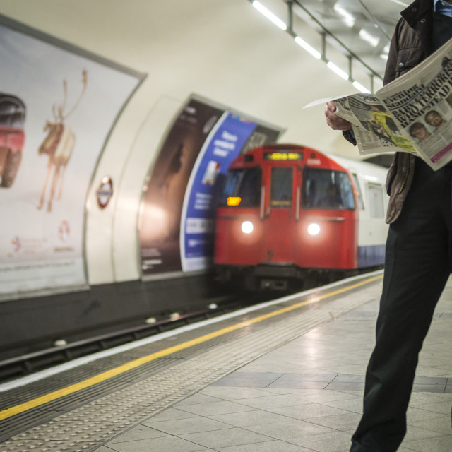 """Man Reading Newspaper Waiting For Underground Train"" stock image"