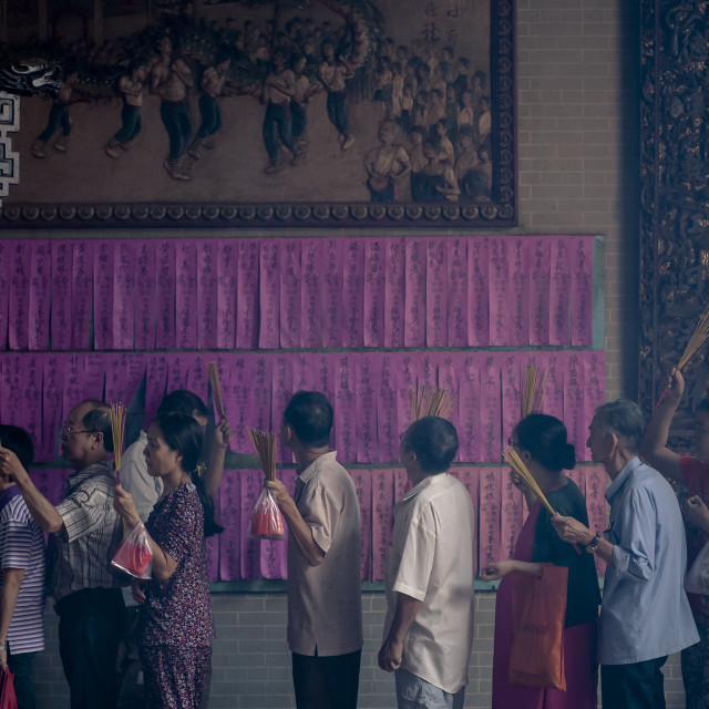 """People getting in line, holding burning incense sticks for their turn of praying."" stock image"