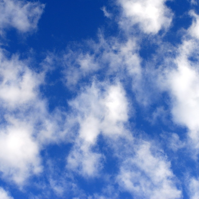 """Fluffy White Clouds against a Blue Sky"" stock image"