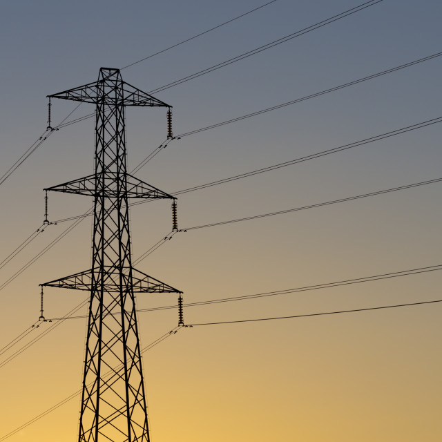 """Electricity pylon in golden sunset glow"" stock image"